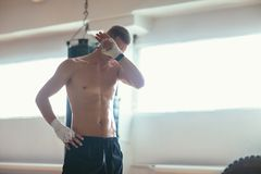 Athlete man wiping the sweat after hard workout. Sport concept royalty free stock photo