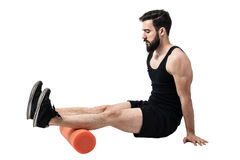 Athlete massaging and stretching hamstring leg muscles on foam roller. Royalty Free Stock Photos