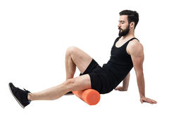 Athlete massaging and stretching legs calf muscles with foam roller. Full body length portrait isolated on white studio background Stock Photography