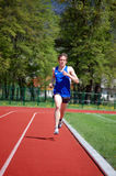 Athlete Measuring Time. Young athlete running at the running track holding a stopwatch Royalty Free Stock Photography