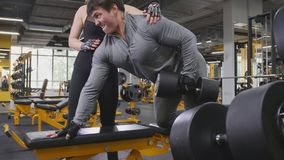 Athlete man lifting dumbbells - training in the gym, attractive girl looks at him. Athlete men lifting dumbbells - training in the gym, attractive girl looks at Stock Images