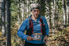 Athlete middle-aged man runs through forest Royalty Free Stock Photo