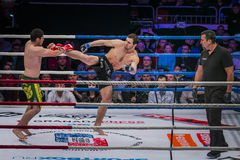 Athlete mixed martial arts fighter gets direct foot kick to his opponent Stock Photos