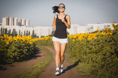 Athlete on morning jog on the sunflower's field Royalty Free Stock Images