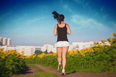 Athlete on morning jog in the sunflower's field Royalty Free Stock Photography