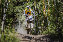 Athlete motorcyclist riding along a forest Stock Images