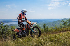Athlete motorcyclist riding on mountain in background of mountains and lake Stock Images