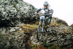 Athlete at the mountain bike down the cliff. Magnitogorsk, Russia -  September 12, 2015: athlete at the mountain bike down the cliff during Urals Cup of downhill Royalty Free Stock Photography