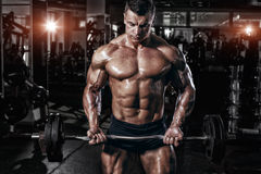 Athlete muscular bodybuilder in the gym training with bar royalty free stock images
