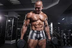 Athlete muscular bodybuilder in the gym training biceps Royalty Free Stock Image