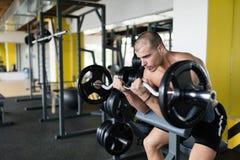 Athlete muscular bodybuilder in gym training biceps Stock Photo