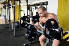 Athlete muscular bodybuilder in gym training biceps Stock Photos