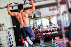 Athlete muscular fitness male model pulling up on horizontal bar. In a gym Royalty Free Stock Photos