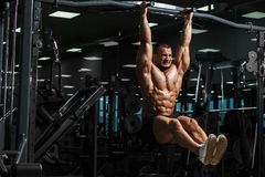 Athlete muscular fitness male model pulling up on horizontal bar. Athlete muscular fitness bodybuilder male model pulling up and doing crunches on horizontal bar Royalty Free Stock Image