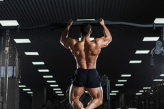 Athlete muscular fitness male model pulling up on horizontal bar Royalty Free Stock Photography