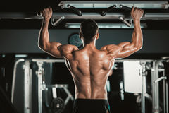 Athlete muscular fitness male model pulling up on horizontal bar in a gym Royalty Free Stock Photos