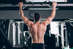 Athlete muscular fitness male model pulling up on horizontal bar in a gym Stock Photos
