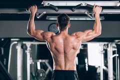 Athlete muscular fitness male model pulling up on horizontal bar in a gym Royalty Free Stock Image