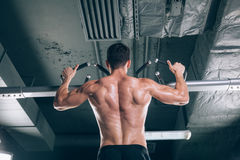Athlete muscular fitness male model pulling up on horizontal bar in a gym Stock Image