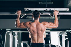 Athlete muscular fitness male model pulling up on horizontal bar in a gym Royalty Free Stock Photography