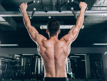 Athlete muscular fitness male model pulling up on horizontal bar in a gym Stock Images