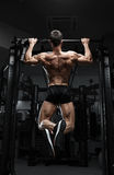 Athlete muscular fitness male model pulling up on horizontal bar Stock Photos