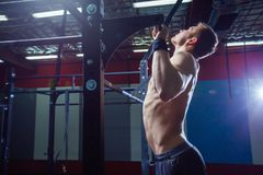 Athlete muscular fitness male model pulling up on horizontal bar in a gym. Cross fit style. Athlete muscular fitness male model pulling up on horizontal bar in a Royalty Free Stock Images