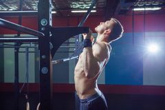 Athlete muscular fitness male model pulling up on horizontal bar in a gym. Cross fit style. Athlete muscular fitness male model pulling up on horizontal bar in a Royalty Free Stock Photography