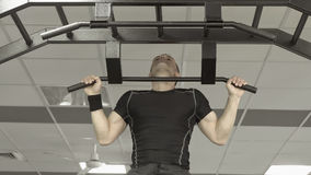 Athlete muscular fitness male model pulling up on horizontal bar in a gym. Stock Images