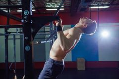 Athlete muscular fitness male model pulling up on horizontal bar in a gym. Cross fit style. Athlete muscular fitness male model pulling up on horizontal bar in a Stock Photo