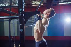 Athlete muscular fitness male model pulling up on horizontal bar in a gym. Crossfit style Royalty Free Stock Images