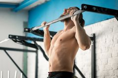 Athlete muscular fitness male model pulling up on horizontal bar in a gym. Strong fit caucasian man doing pull ups on horizontal bar in gym. sports, gymnastics Stock Photos