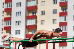 Athlete muscular fitness male model pulling up on horizontal bar on the outdoor. Stock Photography