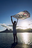Athlete with Olympic Flag Lagoa Sunset Rio de Janeiro Brazil. RIO DE JANEIRO, BRAZIL - MARCH 05, 2015: Athlete holds Olympic flag above sunset city skyline view Stock Photography