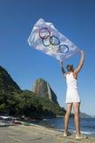 Athlete with Olympic Flag Rio de Janeiro Brazil. RIO DE JANEIRO, BRAZIL - MARCH 24, 2015: Athlete stands at Red Beach (Praia Vermelha) holding an Olympic flag in royalty free stock photos