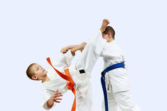 The athlete with the orange belt beats athlete with a blue belt blow leg on the head. Athlete with the orange belt beats athlete with a blue belt blow leg on the royalty free stock image