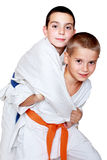 An athlete with an orange belt done a grab for throwing athlete with a blue belt Stock Images