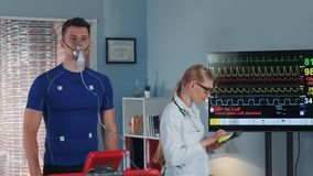 Athlete in oxygen mask doing stress test while cardiologist with tablet monitoring his EKG on display. In modern scientific sports laboratory stock video