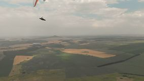 Athlete paraglider flies on his paraglider next to the swallows. Follow-up shooting from the drone.  stock footage