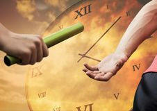 Athlete passing the baton to teammate against clock background. Digitally composite of athlete passing the baton to teammate against clock background stock photography
