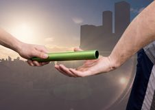 Athlete passing the baton to teammate. Hand of athlete passing the baton to teammate against digitally composite cityscape background stock photo