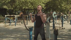 Athlete performing biceps curls with barbell. Determined muscular fit man training with barbell, doing biceps curls for chest muscle during outdoor workout stock video footage