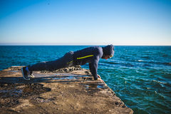 Athlete performing exercises on beach Royalty Free Stock Images