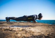 Athlete performing exercises on beach Royalty Free Stock Photos