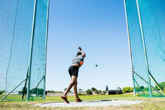 Athlete performing a hammer throw. Determined athlete performing a hammer throw in stadium stock photography