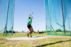 Athlete performing a hammer throw. Rear view of athlete performing a hammer throw in stadium royalty free stock photos