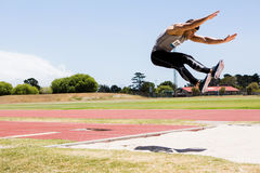 Athlete performing a long jump royalty free stock photography