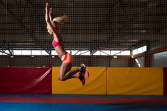 Athlete Performing a Long Jump In Gym royalty free stock images