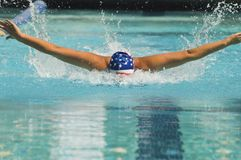 Athlete Performs A Butterfly Stroke. Female athlete performs a butterfly stroke during a swimming race stock photo