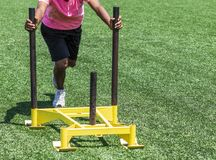 Athlete in pink shirt pushing a sled on turf royalty free stock photography